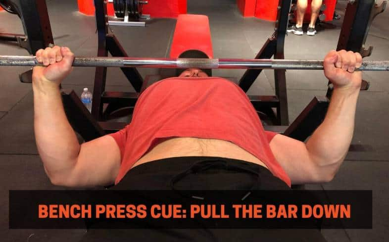 Bench press cue showing the lats engaged as the lifter pulls the barbell down toward the chest