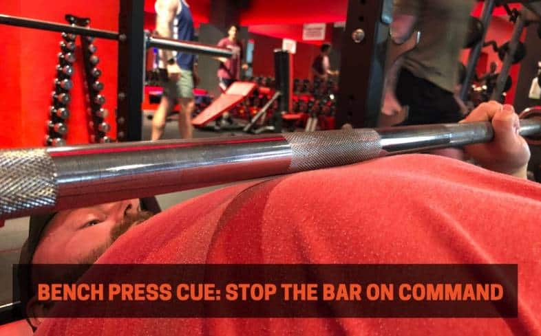 bench press cue showing the barbell stopping right on top of the chest