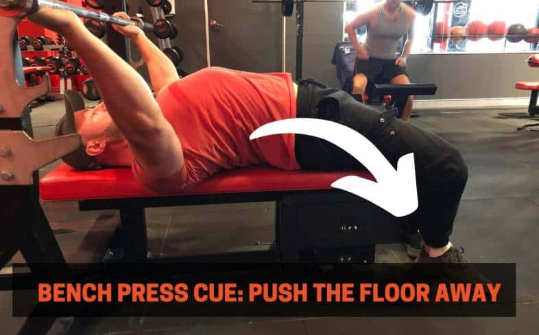Bench press cue showing pushing the floor away