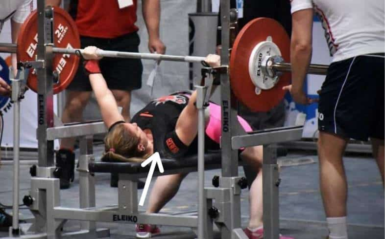 A powerlifter using leg drive to get as high as possible on their traps while laying on the bench press.