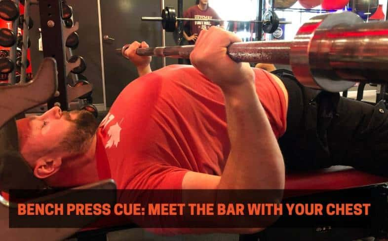 Bench press cue showing the chest meeting the barbell