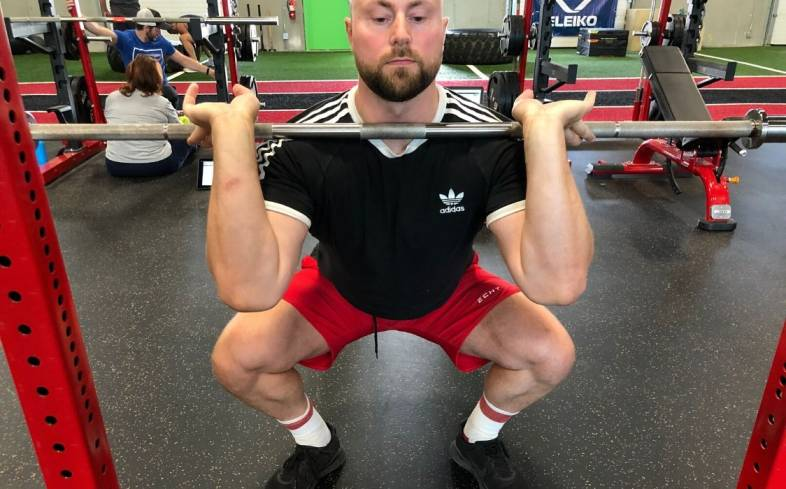 The front squat is a barbell squat variation where the load is placed on the front of the shoulders.