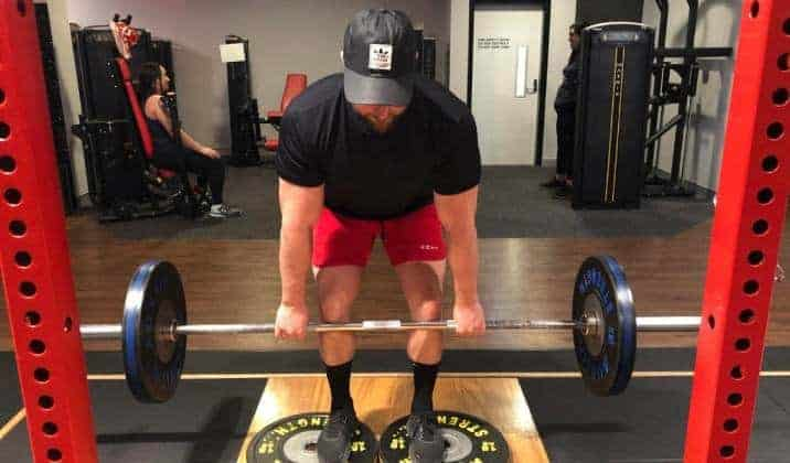 deficit deadlift is performed while standing on an elevated surface ranging from 1-4 inches, such as a weight plate or small riser