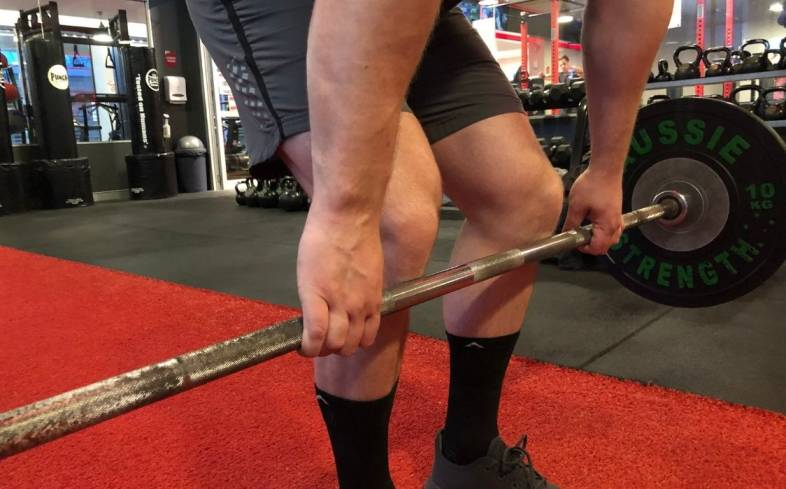 "as you pick the barbell off the floor, you should be thinking about ""pushing the floor away"