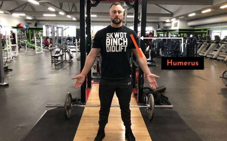 the longer the humerus, the lower the elbow is and so the lower the barbell will touch on your chest