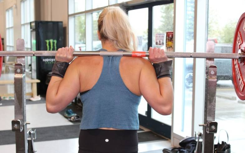 a regular grip is characterized by having four fingers wrapped around the barbell with the thumb tucked underneath the bar