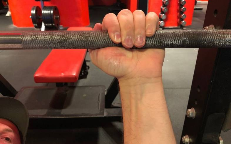 suicide grip can be useful in forcing you to tuck your elbows more on the bench press