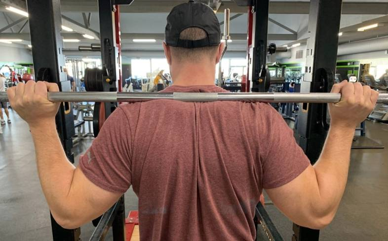 a high bar squat will sit on the upper trap muscles, somewhere above the rear deltoid