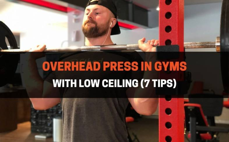you can overhead press with low ceilings by avoiding performing them in an upright stance