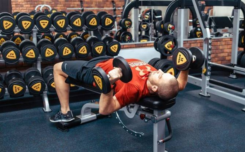 dumbbell bench press allows for greater ranges of motion, which can allow for greater recruitment of the pecs and triceps